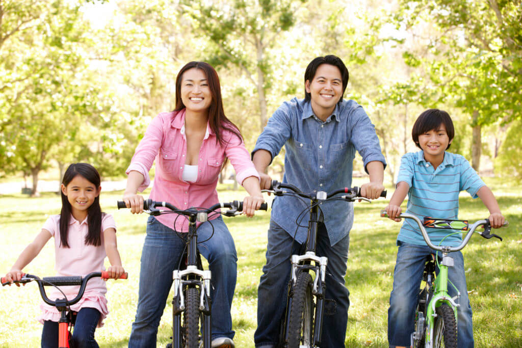Asian family riding bikes with 2 children who both go to Cibolo Pediatric Dentistry and Orthodontics in Cibolo, TX for pediatric dentistry services.