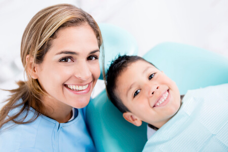 Dentist with a young patient looking very happy because of sedation dentistry options that helped him manager his anxiety about treatment.