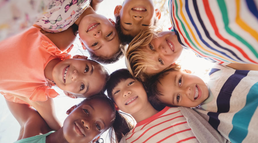 Looking up into a huddle of children at Cibolo Pediatric Dentistry and Orthodontics in Cibolo, TX