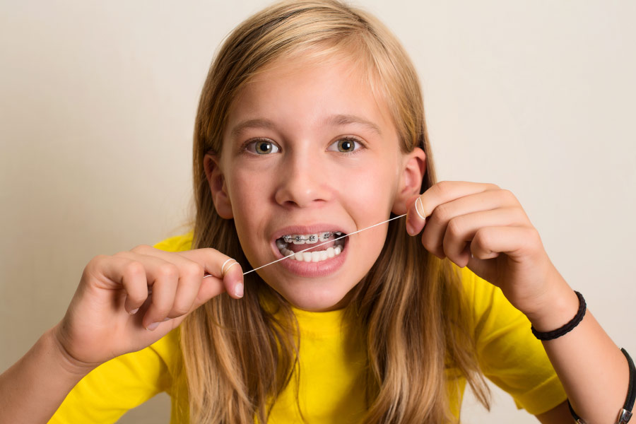Blonde girl in a yellow shirt flosses with braces on her top teeth