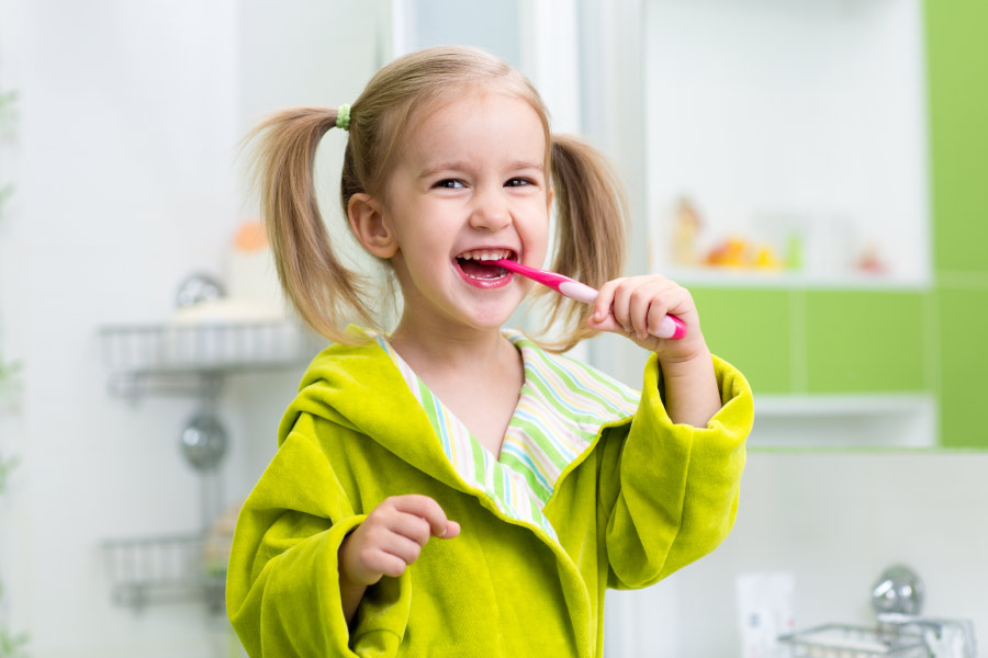 Little girl with blond pigtails and a lime green bathrobe brushing her teeth