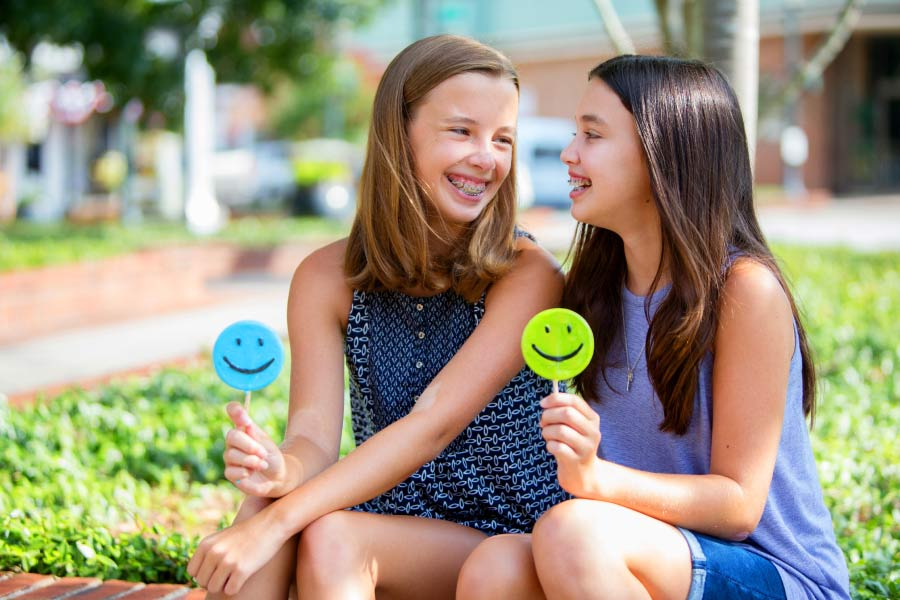 Two girls with braces sitting on the curb and smiling