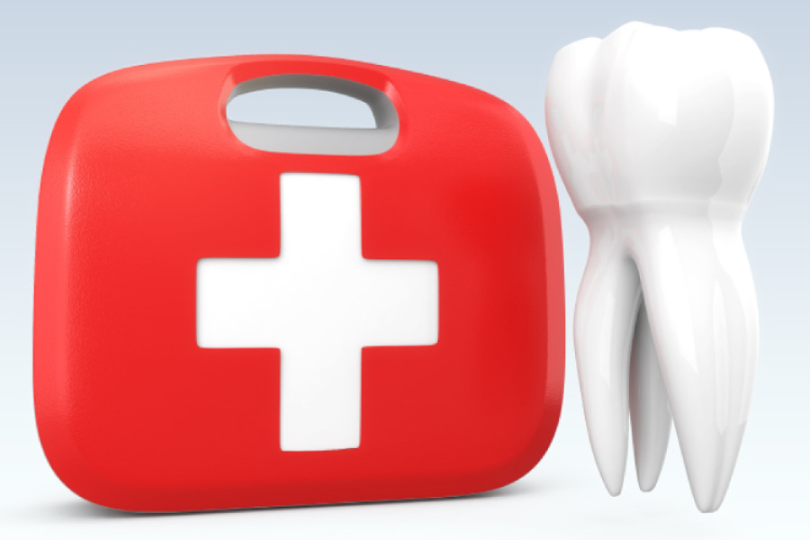 Emergency kit with a white cross next to a model of a tooth