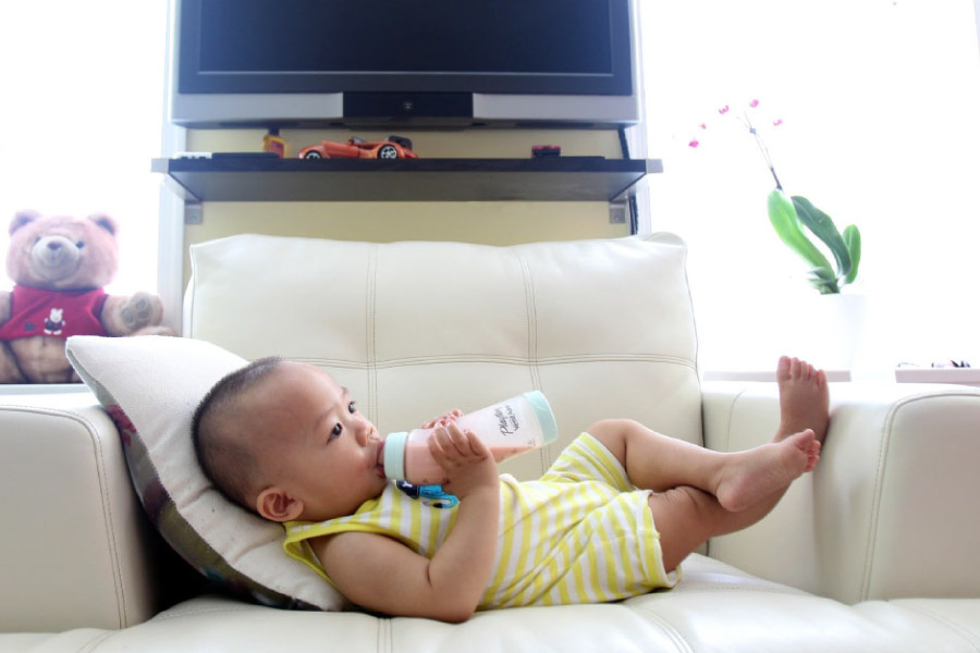 Asian baby reclining on the couch with a bottle.