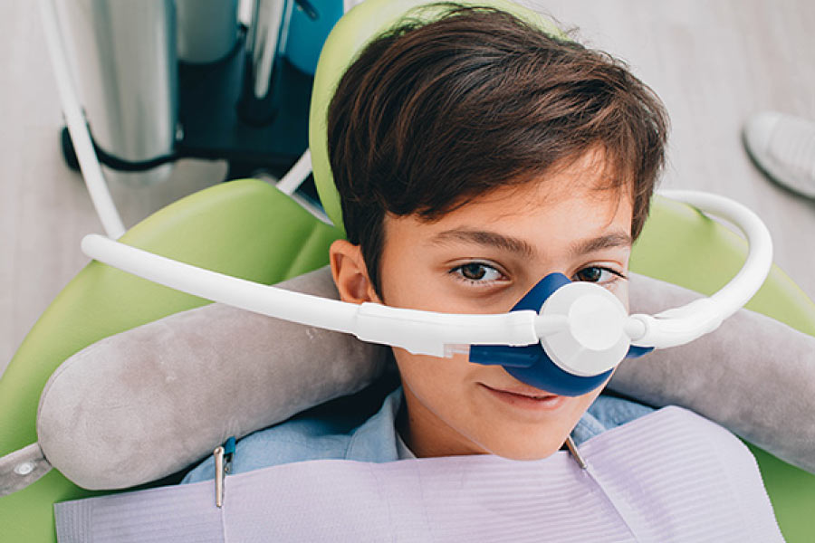 Young boy in the dental chair wearing a nitrous oxide or laughing gas mask for dental sedation.
